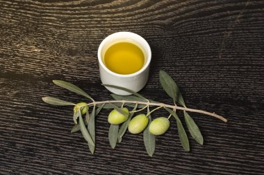 Branch of olive tree with green olive berries and cap of fresh o