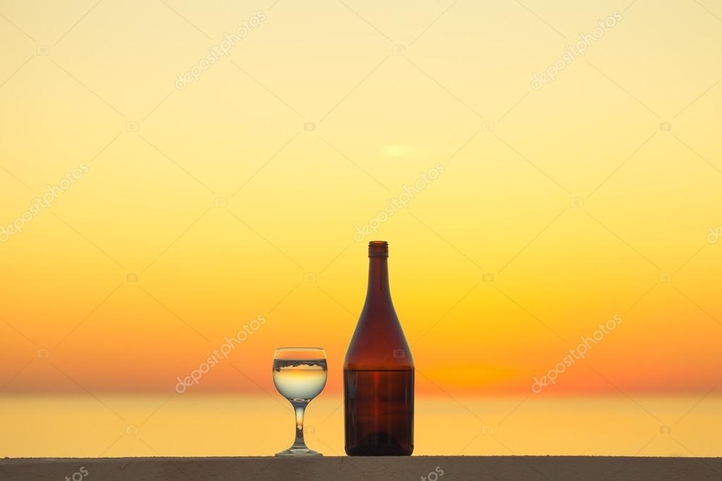 Brown bottle and glass of white vine with reflections of houses