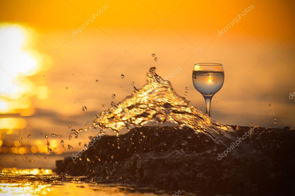 Glass of white vine with reflections of sun and sea on the backg