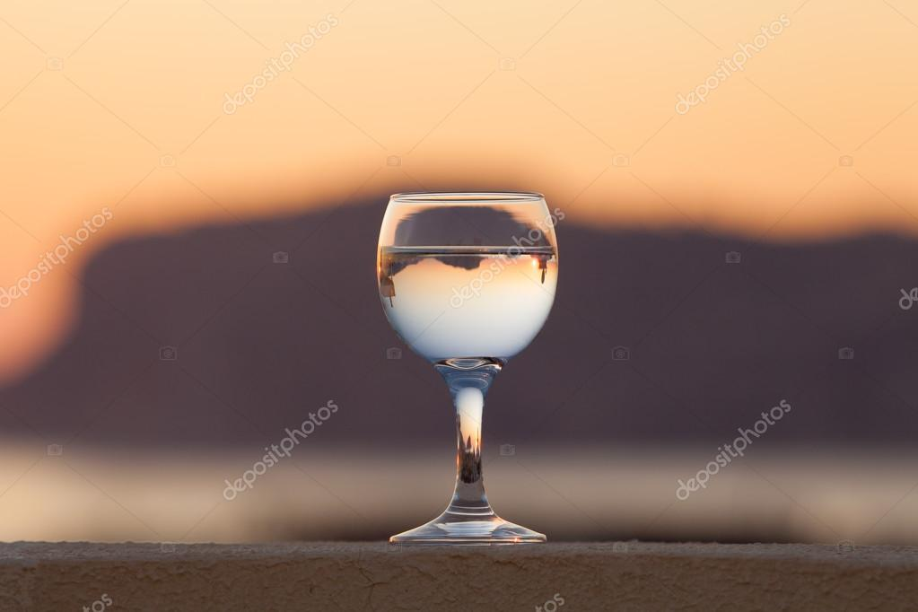 Glass of white vine with reflections of houses and view to beaut
