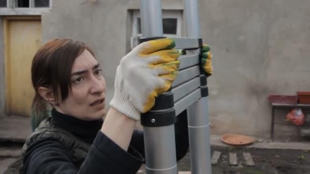 Žena položí žebřík ve dvoře