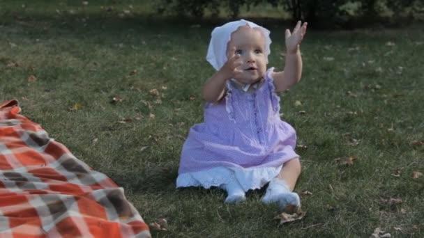 Děvčátko sedící v trávě vyvolává její ruce