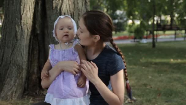 Una giovane bambinaia toccando un bambino ragazza s naso. La bambina si sfrega il naso