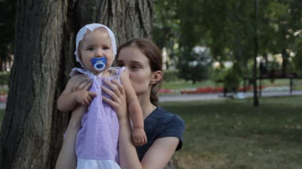 Una tata molto giovane, avere una bambina con un ciuccio in grembo