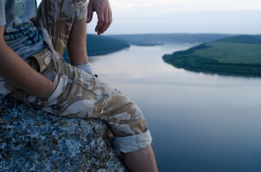 man sitting on a rock above the river at sunset