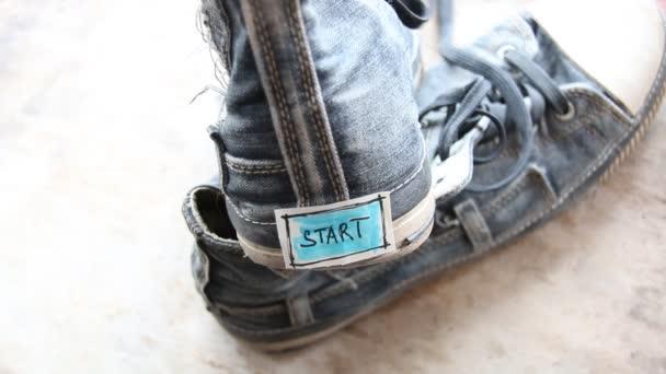 Tag mit dem Wort Start auf Turnschuhen.