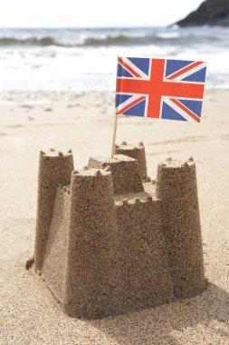 Sandcastle On Beach With Union Jack Flag