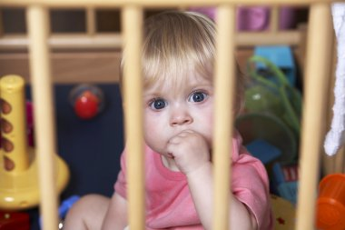Toddler Looking Sad And Neglected In Playpen