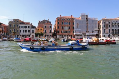 Courier barge full of parcels navigating the Grand canal in Venice, Italy