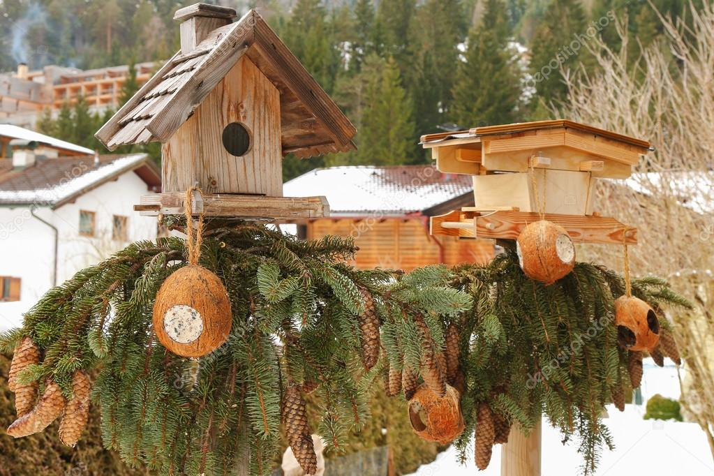 Two wooden bird feeders with coconut shell suet treats hanging