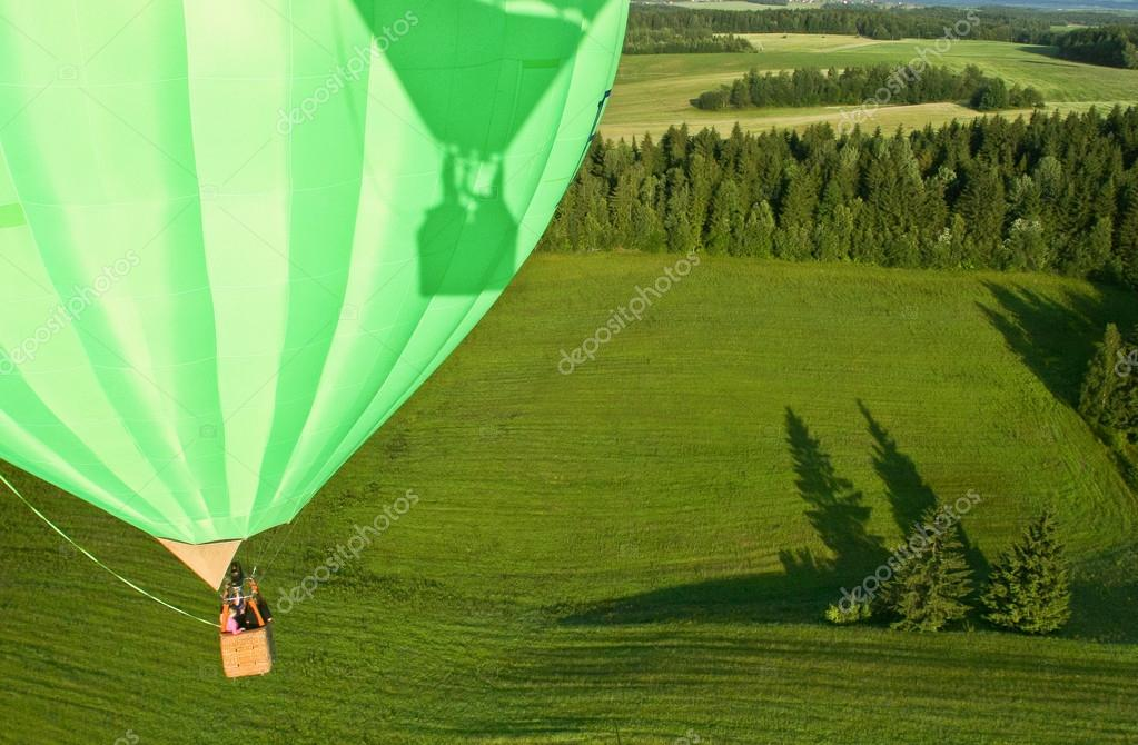 Hot air balloon over the field with blue sky, close up