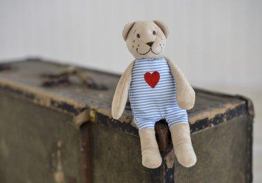 Old Bear toy sitting on retro suitcase, on beige background