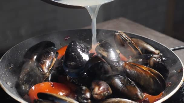Luxusrestaurant. Köstliche Muscheln mit heißem Dampf zubereiten. Zeitlupe. Teller mit Flüssigkeit übergießen. Traditionelle mediterrane Küche. Pasta mit Meeresfrüchten. Volle Konzentration