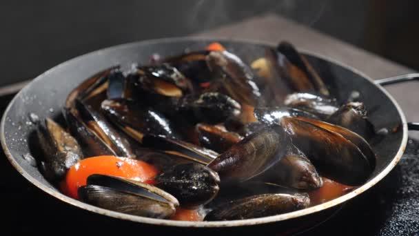 Chef kocht Muscheln in der Pfanne. Zeitlupe Food-Video. Prozess der Zubereitung italienischer Pasta mit Muscheln in Tomatensauce. Traditionelle mediterrane Küche. Heißer Dampf steigt auf. Volle Konzentration