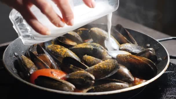 Luxusrestaurant. Köstliche Muscheln mit heißem Dampf zubereiten. Zeitlupe. Auflauf mit Milch übergießen. Traditionelle mediterrane Küche. Pasta mit Meeresfrüchten. Volle Konzentration