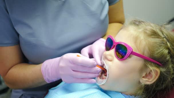Hezké dívce se léčí zuby. Záběr zblízka. Moderní stomatologie. Dítě ve slunečních brýlích si nechává vyléčit zub. Vysavač v rukou zubaře. Dítě sedí na zubním křesle. 4 k