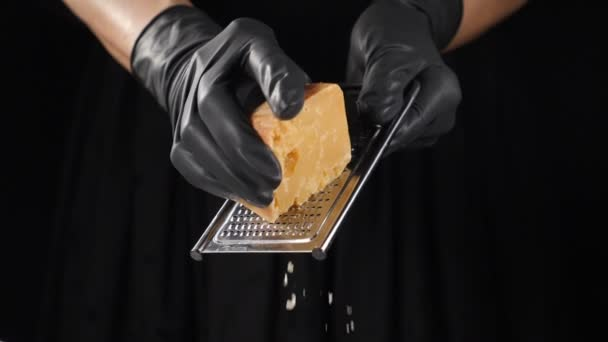 Italská kuchyně, strouhání sýrů, vaření a servírování jídel v restauraci. Šéfkuchař v černých rukavicích strouhá lahodný tvrdý sýr na struhadle. Zpomal. Černé pozadí. Full hd