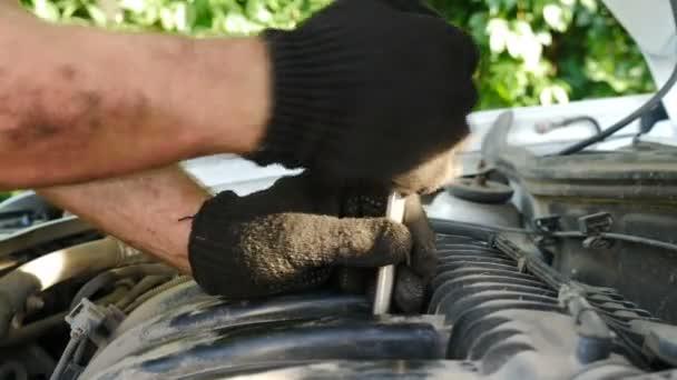 Automechanici v rukavicích opravují auto na čerpací stanici. Automobilový mechanik používající klíč k opravě motoru, autoservis. Nové náhradní díly. opravárenské centrum. Záběr zblízka. 4 k video