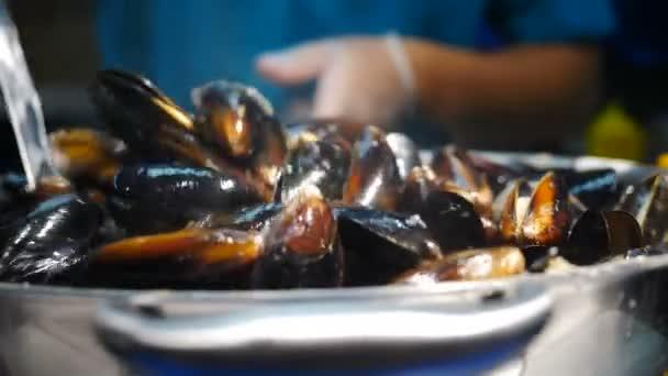 Street Food Miesmuscheln und Muscheln. Kochen und Mischen von Meeresfrüchten mit würziger Sauce große Pfanne. Verkauf von Streetfood auf lokalen Märkten oder Festivals. Mediterrane Küche. Auf großer Pfanne braten, kochen lassen