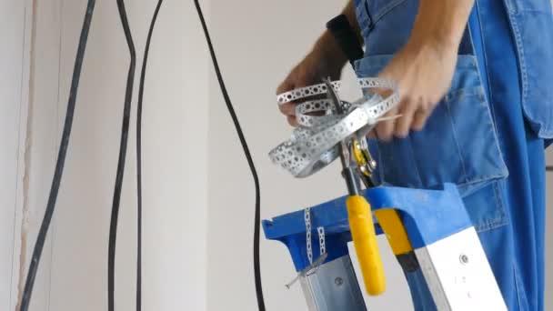 Instalace elektrického vedení na stropě bytu. Nastavení elektrického kabelu. Elektrikář opravuje dráty. Zlepšení domu. Elektrikář umístil elektrický kabel do montované budovy. 4 k