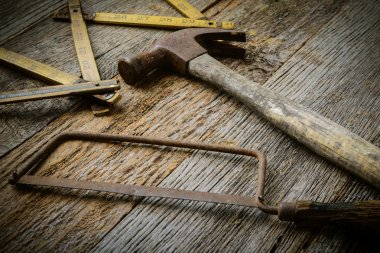 Hammer, Saw and Measuring Tape on Rustic Wood Background