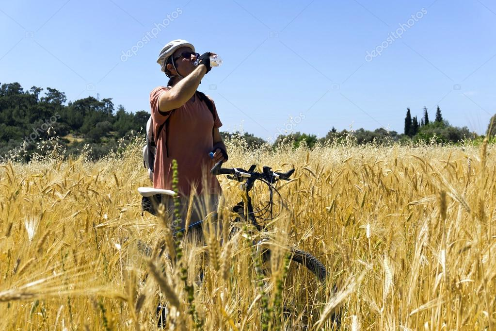 Cyclist man is resting ia gleanings field