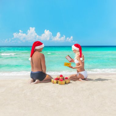 Happy couple at beach in santa hats making presents for christma