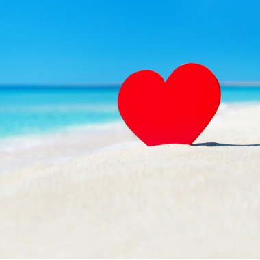 Red heart in sand