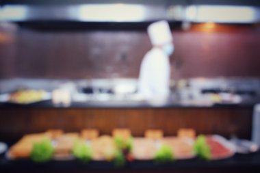 Blurred of restaurant kitchen with chef
