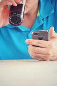 Muž chytrý telefon s cola nápoj