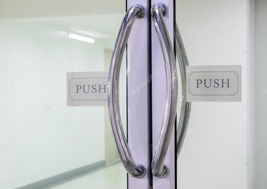 Chrome Handles With Push Sign On Glass Door Stock Photo