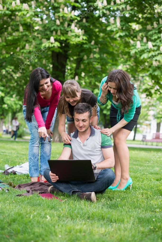 Group of Teenage Students at Park with Computer