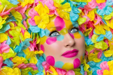 Closeup of young woman face in colorful flower petals. Beauty shot. Face paint. stock vector