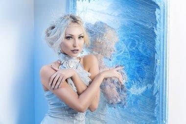 Snow queen near frozen mirror