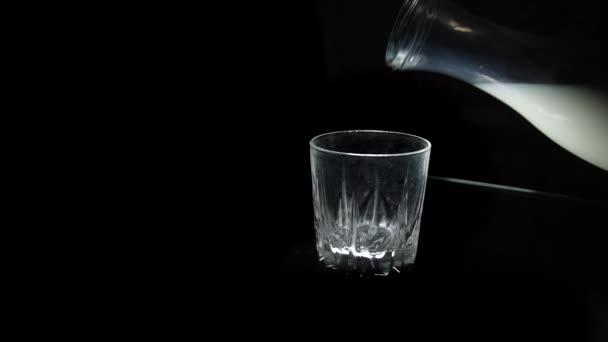Nalijte mléko ve skle na černém pozadí