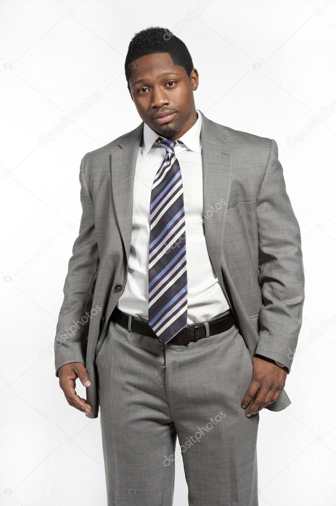 7a07b85f478 Attractive African American male model wearing a gray suit with a modern tie  posing in a studio on a white background while looking at the camera —  Photo by ...