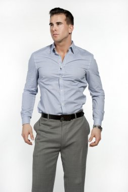 Athletic and attractive caucasian male wearing a fitted blue shirt and gray suit pants in a studio setting on a white background posing and looking to the left stock vector