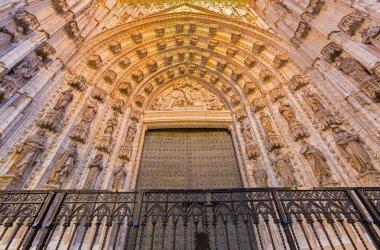 SEVILLE, SPAIN - OCTOBER 28, 2014: The main west portal (Puerta de la Asuncion) of Cathedral de Santa Maria de la Sede by Pedro de Toledo, J. de Hoces, F.de Rosales for neo-gothic part.