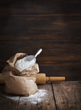 Flour in paper bag on wooden background.
