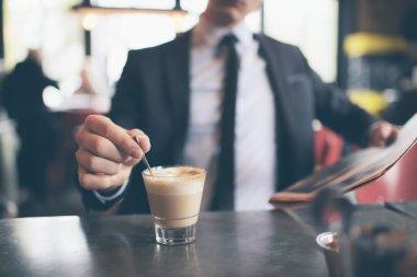 Hand of businessman stirring coffee