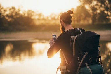 Backpacker photographing landscape with smartphone