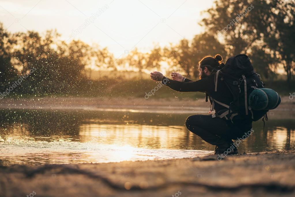 Backpacker at lake playing with water