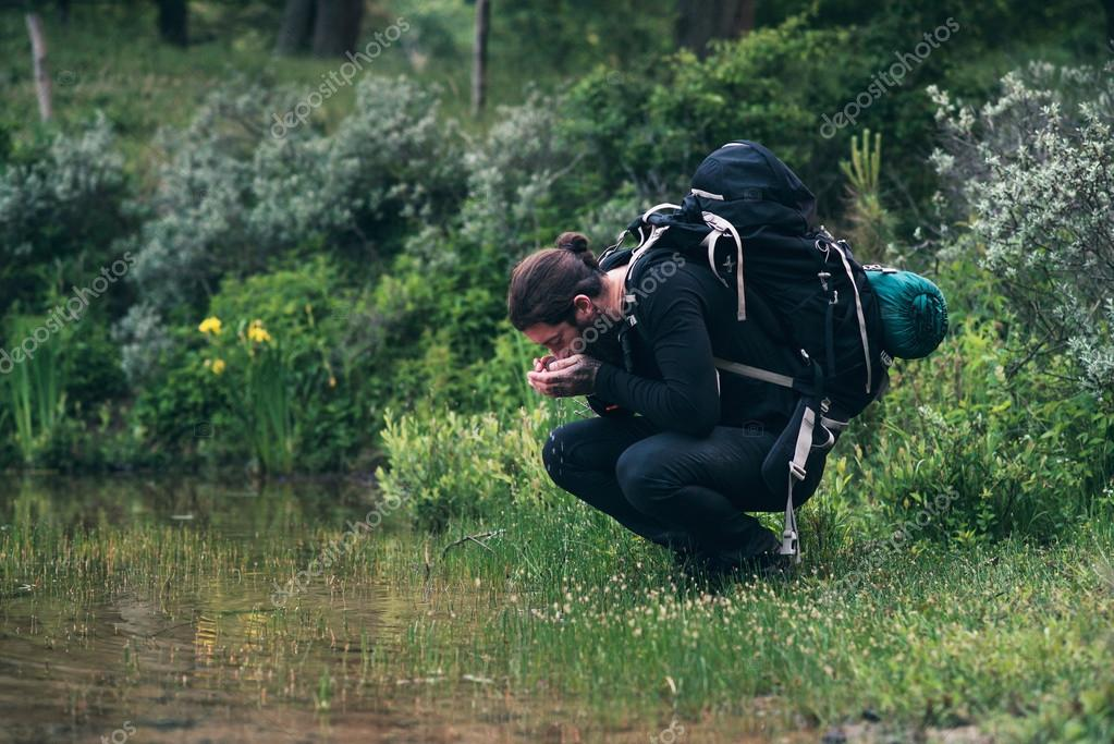 Hiker with backpack drinking water