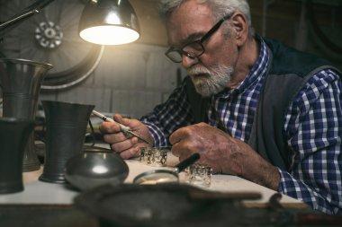 Man soldering metal rings