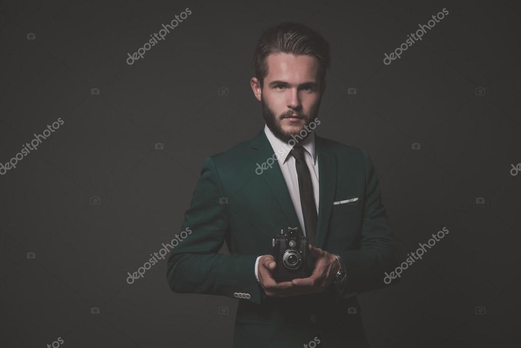 ac900ef33a49c Biznes moda mężczyzna nosi zielony garnitur z białą koszulę i czarny  krawat. przytrzymanie starodawny aparat. wyśmienity przeciwko szary —  Zdjęcie od ...