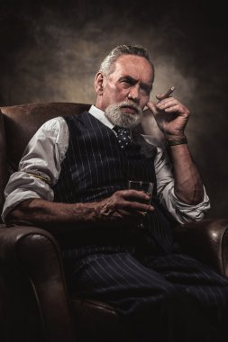 In chair sitting senior business man with cigar and whisky. Gray
