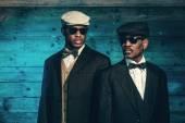 Zwei Vintage afrikanischen amerikanischen Gangster vor alten hölzernen wa