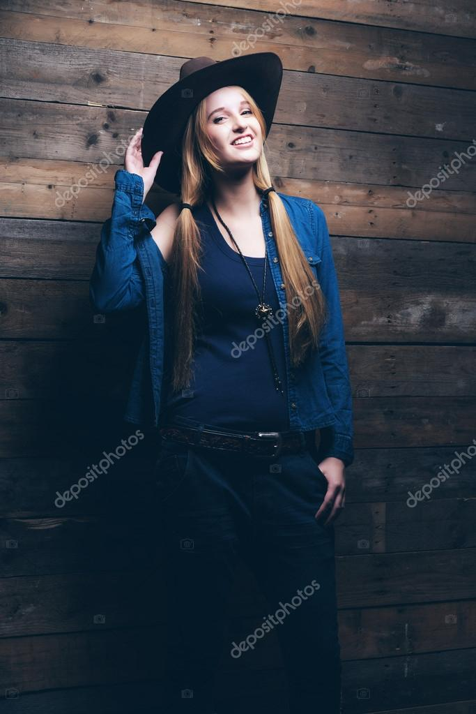 Cowgirl jeans fashion woman with long blonde hair. Standing agai