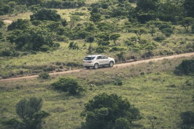 Four wheel drive car driving on dirt road in game reserve. Mpong