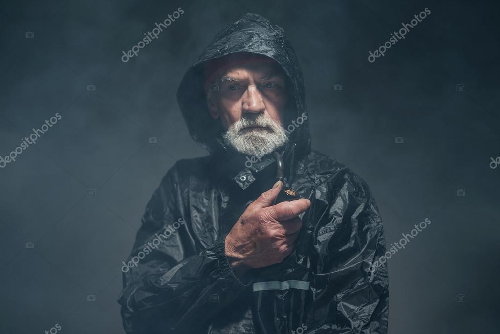 db4ae74656 Vecchio barbuto in impermeabile — Foto Stock © ysbrand #73639357